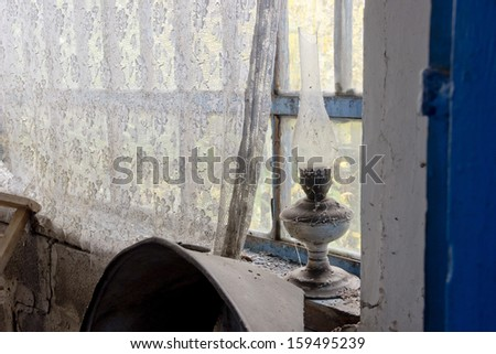 interior of old abandoned room with kerosene lamp - stock photo