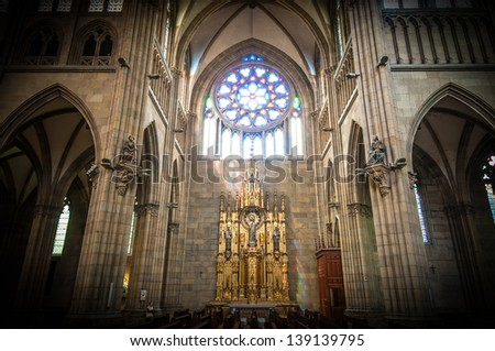 Interior of old catholic church with golden altar in centre, large stained-glass window over it, huge arches and high columns made of grey stone. Religion and faith. Holy places and architecture. - stock photo