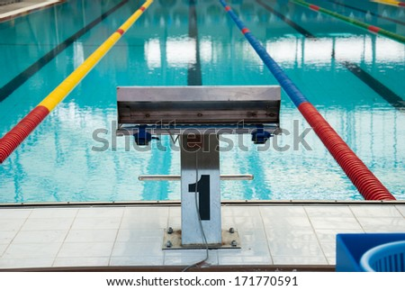 Interior of public indoor swimming pool with racing Lanes and blue water at Suphan Buri - stock photo