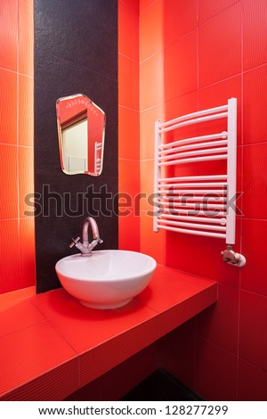 Interior of red bathroom with wash basin and heater - stock photo