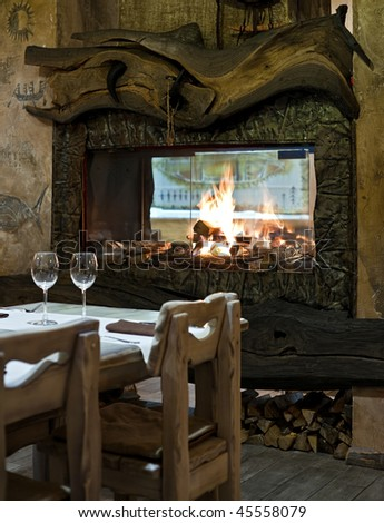 Interior of restaurant with fireplace, wooden rustic furniture and two wineglasses - stock photo