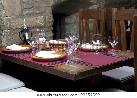 Interior of restaurant with served table and stone wall