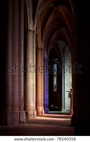 Interior of the ancient gothic cathedral in Southern France. Perspective with stained glass.