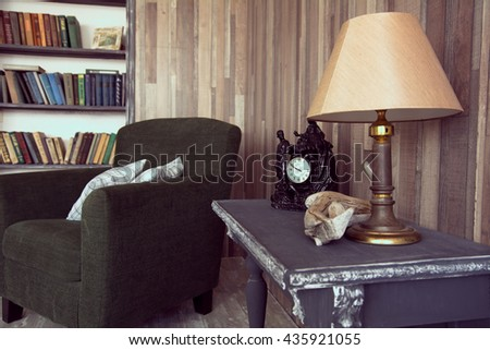 Interior of the cabinet with Antique table lamp. armchair with cushions and books on shelves - stock photo