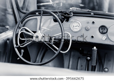 Interior of the old automobile with steering wheel and dashboard. Retro car in vintage style. Old car with manual control for persons with disabilities. - stock photo
