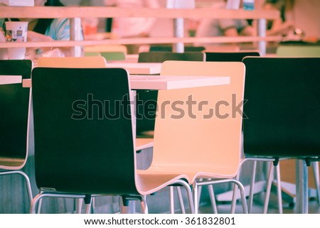 Interior of the restaurant fastfood with bright colored chairs and empty tables without visitors defocus on people background , process in vintage style