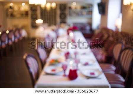 interior of the restaurant,  large table laid for  Banquet, decorated in Burgundy tones, blurred background - stock photo