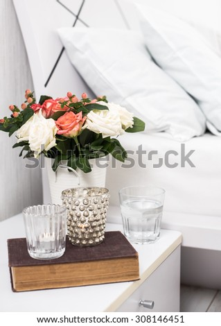 Interior of white bedroom, new linens on the bed, cozy home. Bedside table decor and pillows closeup. - stock photo