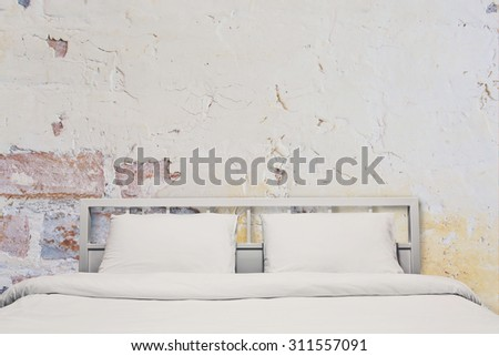 Interior of white bedroom with grunge cement wall background, vintage style - stock photo