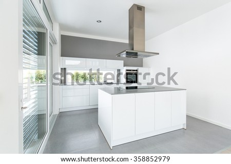 Interior of white kitchen with big windows