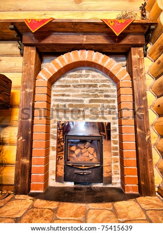 Interior of wooden chalet with small fireplace - stock photo