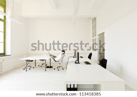 interior, office with modern furniture, man relaxes - stock photo