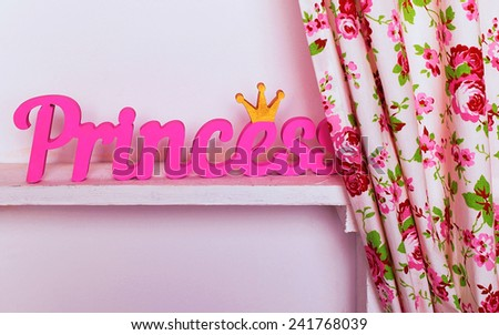 Interior photo of home decor for little princess with pink wooden word is on the shelf of the cupboard near the curtain - stock photo