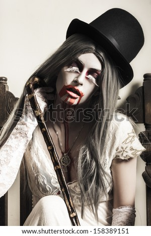 Interior portrait of a grunge ghost girl with blood mouth. Fine art vampire concept - stock photo