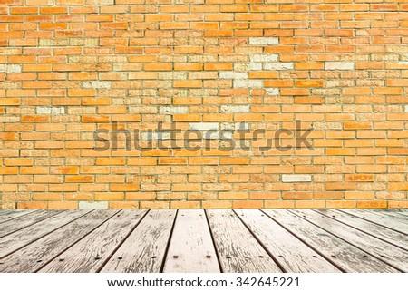 Interior room with orange brick wall and wood floor - stock photo