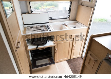 Interior shot of a caravan showing the kitchen area with oven, hob and grill.