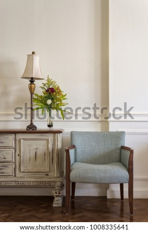 Interior shot of light blue armchair and cream vintage sidebar with table lamp and flowers planter on off white wall and wooden floor