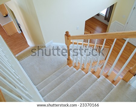 Interior stairway viewed from the landing looking into the foyer and kitchen in a modern home - stock photo
