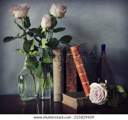 Interior still life, composition of antique books on a wooden table, pink roses in a glass bottle,purple Murano vase on grunge texture, desaturated retro Instagram-like and chiaroscuro effects added - stock photo