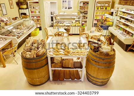 Interior view of a delicatessen with chairs and tables and displays featuring meats, preserves and general supplies as well a display of freshly baked breads and cakes in the foreground - stock photo