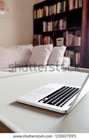 Interior view of a home living room with an open laptop computer on a coffee table in a cozy living room, indoors. - stock photo