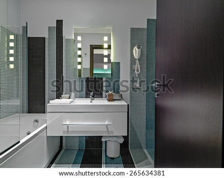 interior view of a modern barthroom in the hotel with mosaic tiles in foreground the washbasin - stock photo