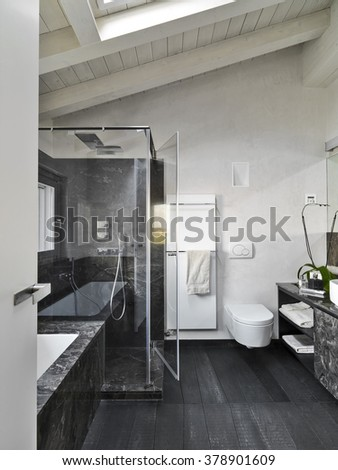 interior view of a modern bathroom in the attic room with wood floor in the foreground the glass shower cubicle - stock photo