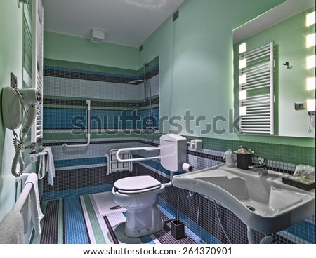 interior view of a modern bathroom whit masonry shower cubicle colored mosaic tiles