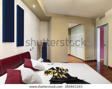 interior view of a modern bedroom whose floor is made of wood with woman dress on the bed overlooking on the wardrobe