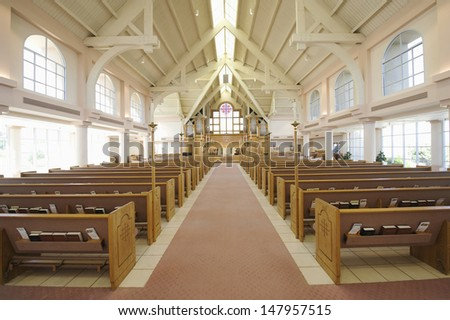 Interior view of a modern church with empty pews - stock photo