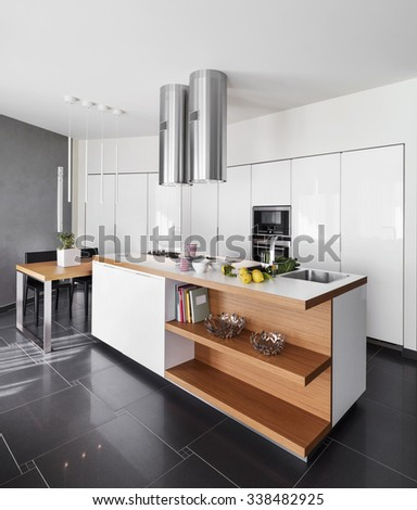 interior view of a modern kitchen island with dining table - stock photo
