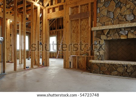 Interior view of a new home under construction. A stone fireplace has been installed. Horizontal shot. - stock photo