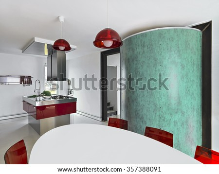 interior view of a red modern kitchen with kitchen island and dining table - stock photo