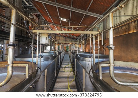 Interior view of a rum plant in Marie Galante, Caribbean, with brewing tanks and pipes to let sugar juice fermentation. - stock photo