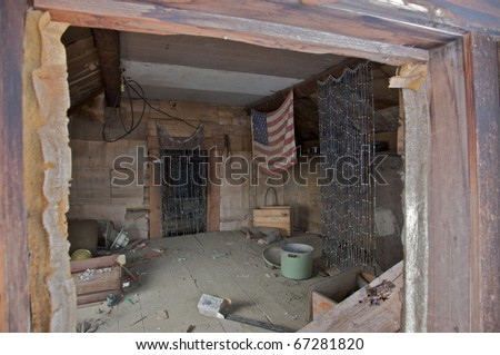 Interior view of an abandoned shack in disrepair.
