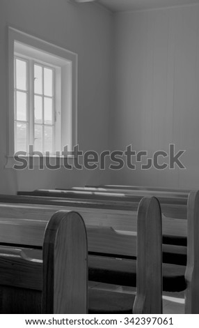 Interior view of an old church with empty pews in black and white - stock photo