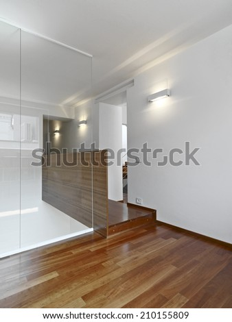 interior view of apartment overlooking on the landing with wood floor and glass banister