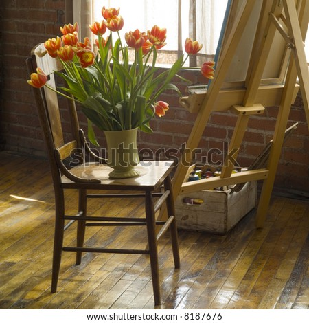 interior view of artist studio with vase of flowers on a chair - stock photo