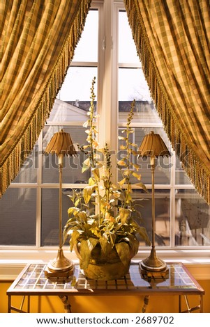 Interior view of window with curtains pulled back and decorative table with lamps and plant. - stock photo