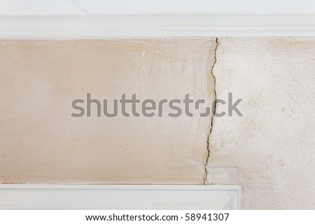 Interior wall with glazed paint shows structural damage from poor foundation. Crack extends from ceiling to window/door frame. - stock photo