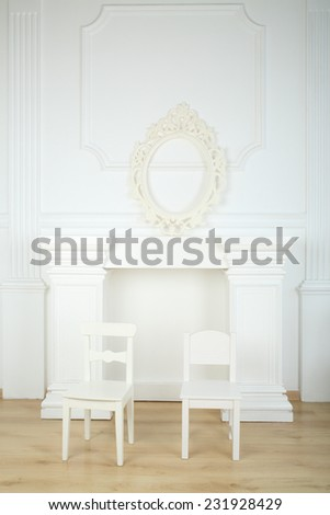 Interior white room with columns in ancient style, fireplace, openwork frame and chairs - stock photo