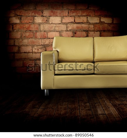 Interior with a coach, wall, wooden floor - stock photo