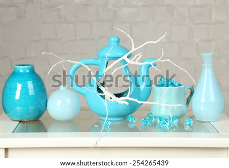 Interior with decorative vases and color branch twig on table top and white brick wall background - stock photo