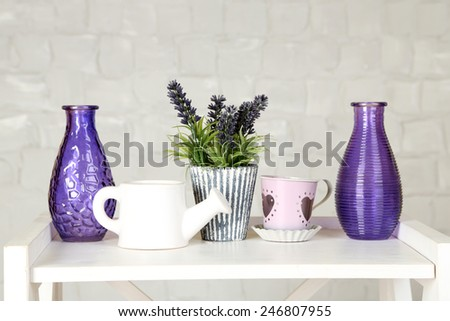 Interior with decorative vases and plant on table top and white brick wall background - stock photo