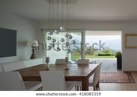 Interiors of new apartment, dining room with old wooden table - stock photo