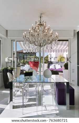 Interiors Shots Of A Modern Dining Room With Glass Table And Old Chandelier Overlooking On The