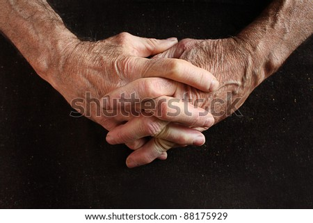 interlaced fingers of old man on black fabric