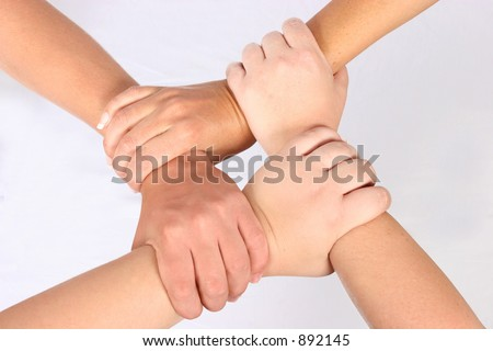 Interlocked hands of four people - stock photo