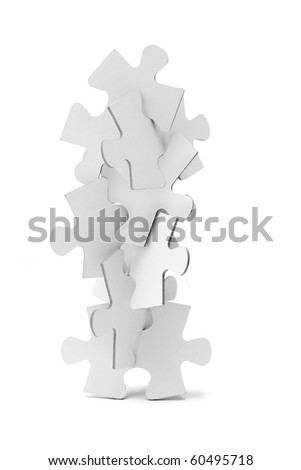 Interlocking pieces of jigsaw puzzles tower on white background