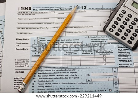 Internal Revenue Service form 1040 with chewed pencil & electronic calculator - stock photo